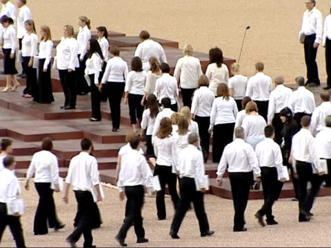 25th anniversary: memorial ceremony at horse guards parade; choir lining up on stage with nutbeem as interviews on screen heard sot - choir stock videos & royalty-free footage