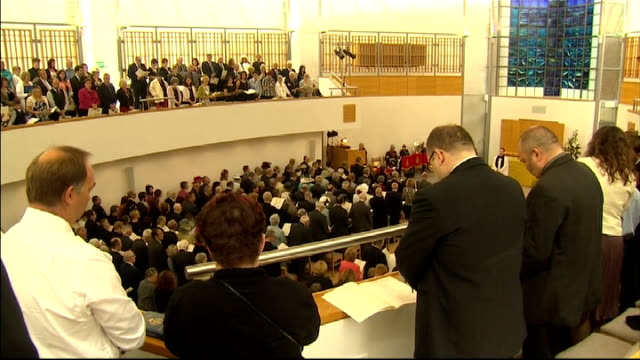 service of remembrance people standing in silence including priest / members of the royal british legion walking up the aisle of the chapel carrying... - altar stock videos & royalty-free footage