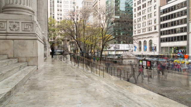 fall afternoon time lapse of people entering and exiting the new york public library's main entrance with traffic along 5th ave in the background - 公共図書館点の映像素材/bロール