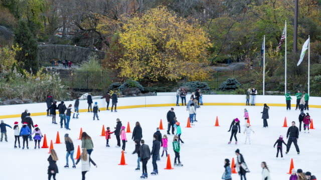 Fall afternoon time lapse of Wollman Rink being emptied of ice skaters, with pedestrians walking across a bridge in Central Park in the background