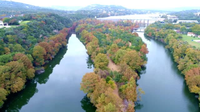vídeos de stock e filmes b-roll de fall colors high above splitting river at red bud isle in austin , texas, usa - town