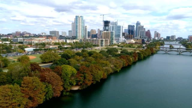 vídeos de stock e filmes b-roll de fall colors tree changing along town lake waters edge a nature view of austin , texas - town