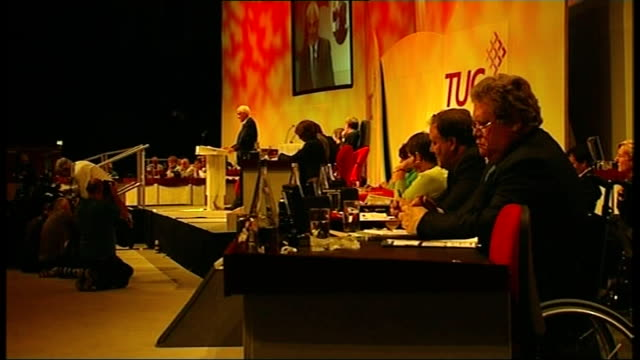 fall in oil prices / alistair darling addresses tuc in brighton; side view darling on stage two tuc delegates seated on deckchairs on beach - 労働組合会議点の映像素材/bロール