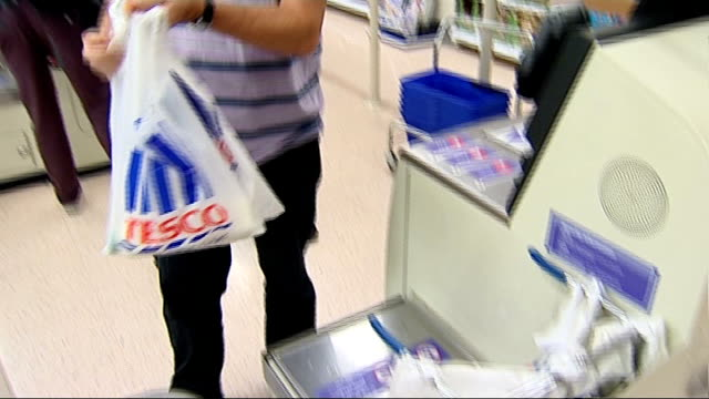 general views inside tesco store various of shoppers at selfservice checkout / man paying for food using chip and pin card reader / man taking... - tesco点の映像素材/bロール