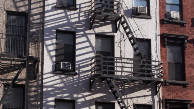 fall shadows street through a fire escape on the side of an apartment building in manhattan. - fire escape stock videos and b-roll footage