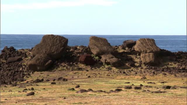 Fallen Moai statues on rocky coast, Easter Island
