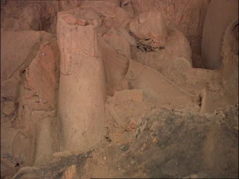 fallen terracotta warriors amongst earth, pan left, museum of qin, xian, china - krieger menschliche tätigkeit stock-videos und b-roll-filmmaterial