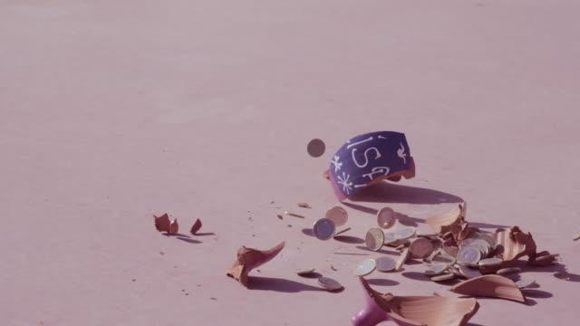 vídeos de stock, filmes e b-roll de falling and broken piggy bank - falência
