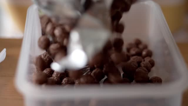 falling chocolate cereal into plastic box, lifestyle concept. - plastic container stock videos & royalty-free footage