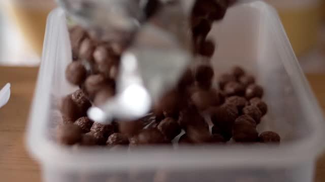 vídeos y material grabado en eventos de stock de caída de cereales de chocolate en caja de plástico, concepto de estilo de vida. - bandeja