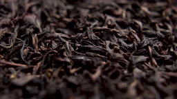 Falling dried black tea leaves close up