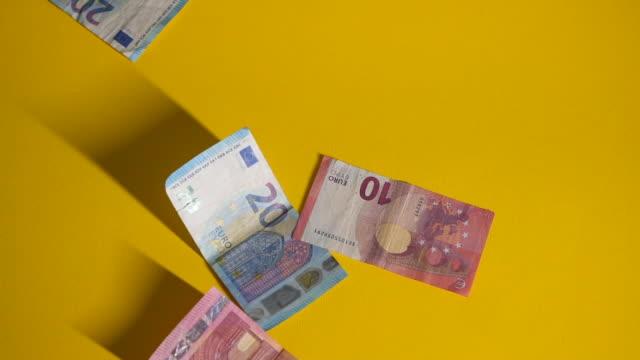 falling euro banknotes on yellow background slow motion - euro symbol stock videos & royalty-free footage