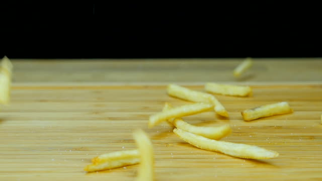 Falling French fries . Close up. Front view. Slow motion.