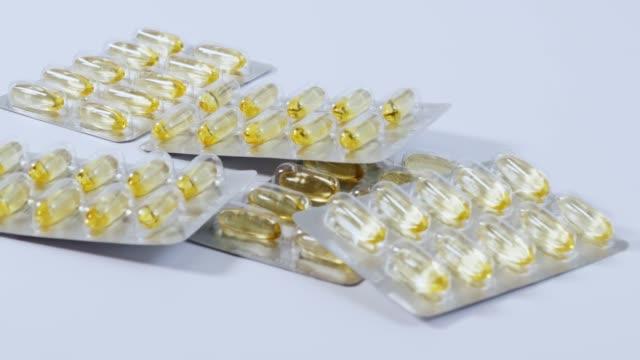 スローモーション錠剤ブリスター パックとは、白い背景の上に落ちる。 - 荷造り点の映像素材/bロール