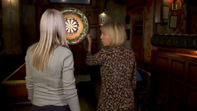 fallon sherrock becomes first woman ever to win a world darts championship match; england: int side view fallon sherrock playing darts in pub close... - ダーツバー点の映像素材/bロール