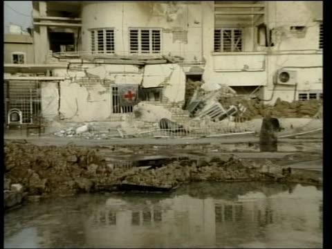 fallujah car bomb; itn wreckage of red cross building which was hit by bomb blast pull out i/c bv connery away to look at red cross building track... - al fallujah stock videos & royalty-free footage