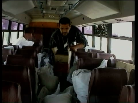 fallujah: ext ground to air us military helicopter flying along us troops on truck as driven along int bus red crescent worker loading aid boxes ext... - アルファルージャ点の映像素材/bロール