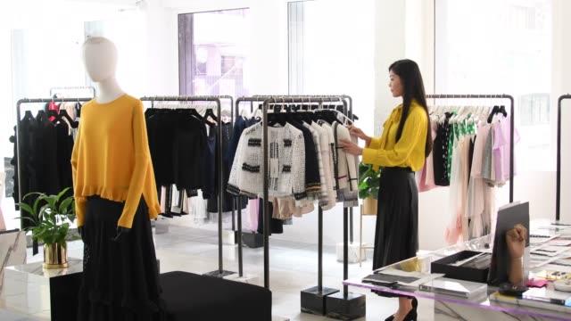 vídeos y material grabado en eventos de stock de famale dependienta en tienda de moda - textil