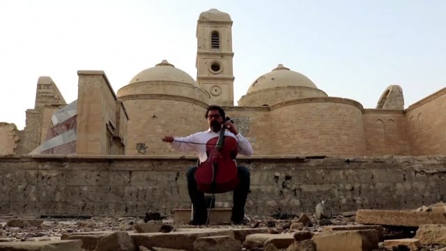 Famed Iraqi maestro and cello player Karim Wasfi performs in front of the Great Mosque of alNuri in Mosul's war ravaged Old City one year after the...