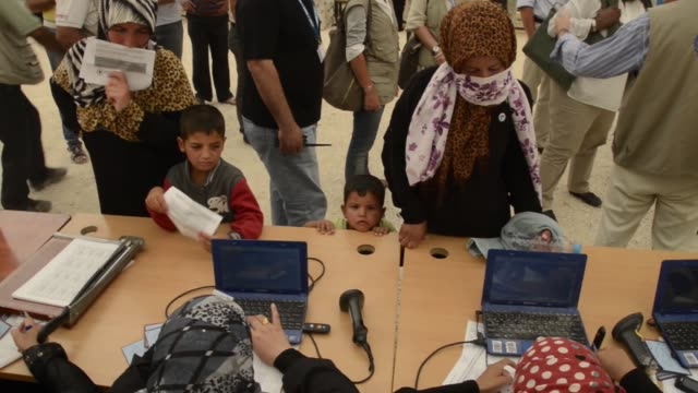 ha families and aid workers processing ids for syrian civil war refugees - シリア難民問題点の映像素材/bロール