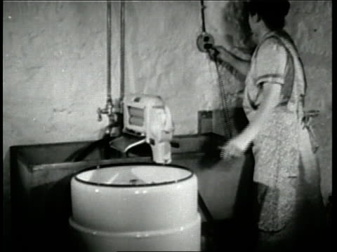 stockvideo's en b-roll-footage met families enjoy the convenience of newlyinvented electrical appliances in the 1930s - 1930