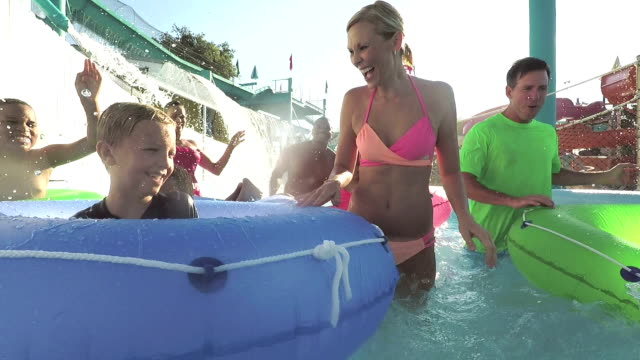 families, friends splashing on lazy river at water park - water park stock videos and b-roll footage