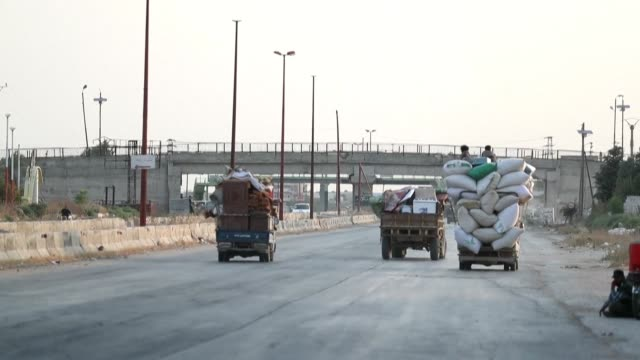 stockvideo's en b-roll-footage met families from syria's southern idlib province and the northern countryside of neighbouring hama flee in trucks loaded with their belongings as... - benen gespreid