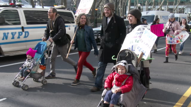 Families holding signs of protest head down 42nd Street to join the Women's March On NYC