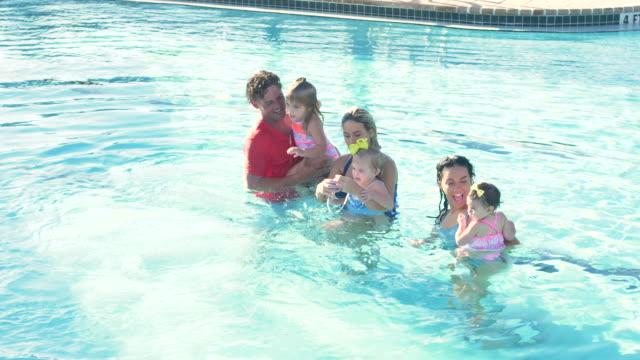 スイミングプールの家族、女の子は父親に泳ぐ - 生後18ヶ月から23ヶ月点の映像素材/bロール