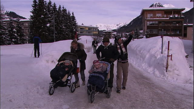 Families push their baby strollers along a snowy path in Davos, Switzerland.