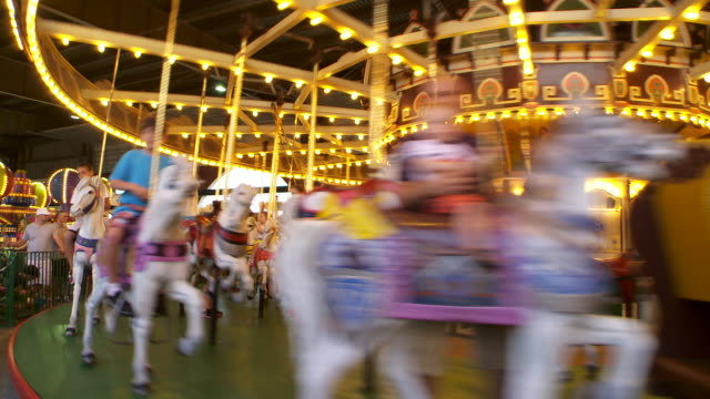 families ride the carousel early evening at an amusement park on the jersey shore - 回転遊具点の映像素材/bロール