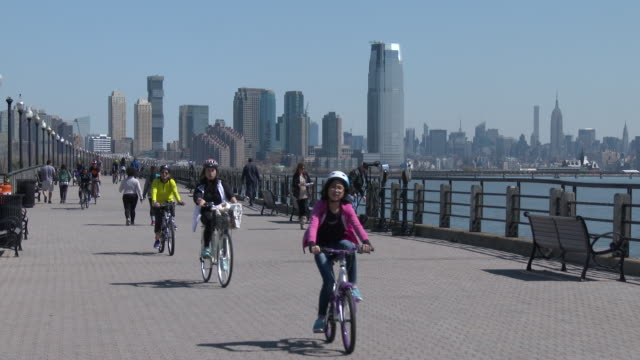 families riding bicycles, spending time outdoors - liberty state park, nj waterfront (manhattan skyline) - promenade stock videos & royalty-free footage