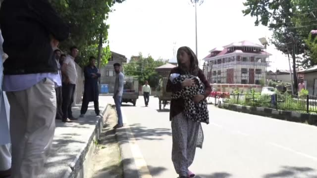 families sit on the pavement outside a police station in kashmir's main city of srinagar waiting to see their loved ones who were swept up in... - station stock videos & royalty-free footage