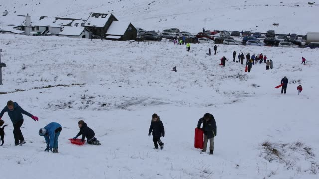 families sledging on top of kirkstone pass in the lake district in winter, uk. - mountain range stock videos & royalty-free footage
