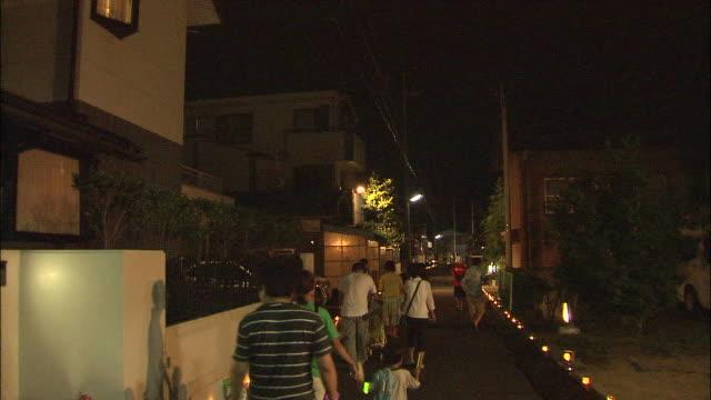 families walk along the ishiakari road, illuminated by stone lamps. - zona pedonale strada transitabile video stock e b–roll