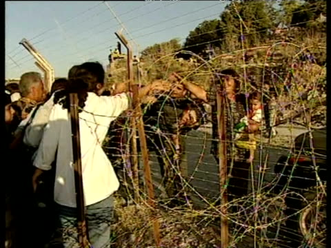 vidéos et rushes de families wave to each other across barbed wire fence at israel/lebanon border may 2000 - groupe moyen d'objets