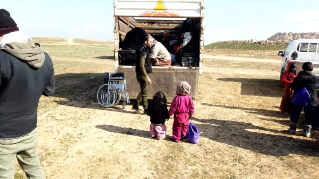 families who fled fighting in bagouz climb aboard a truck after being screened by members of the syrian democratic forces at a makeshift screening... - syrian democratic forces stock videos & royalty-free footage