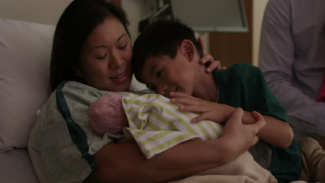 family admiring newborn baby in hospital room - familie mit drei kindern stock-videos und b-roll-filmmaterial