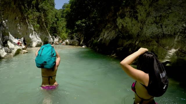 vídeos de stock, filmes e b-roll de aventura familiar, caminhe pelo rio frio da montanha - área arborizada