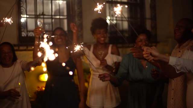 family and friends celebrating new year party with sparkler at home - bahia state stock videos & royalty-free footage