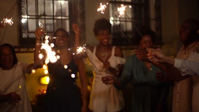 vídeos y material grabado en eventos de stock de familia y amigos celebrando la fiesta de año nuevo con luces de bengala en casa - bahía