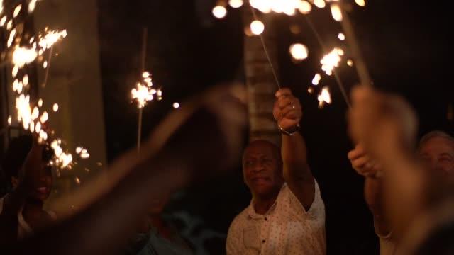 vidéos et rushes de famille et amis célébrant la fête du nouvel an avec cierge magique à la maison - countdown