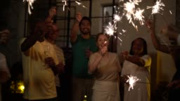 Family and Friends Celebrating New Year Party with Sparkler at Home