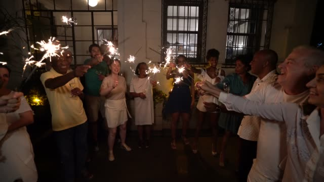 family and friends celebrating new year party with sparkler at home - large family stock videos & royalty-free footage