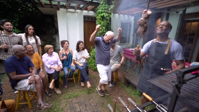 family and friends enjoying a barbecue party at home - barbecue social gathering stock videos & royalty-free footage