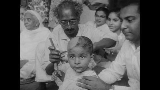 Family and friends gather at a Mundan ceremony where a young child's head is shaved