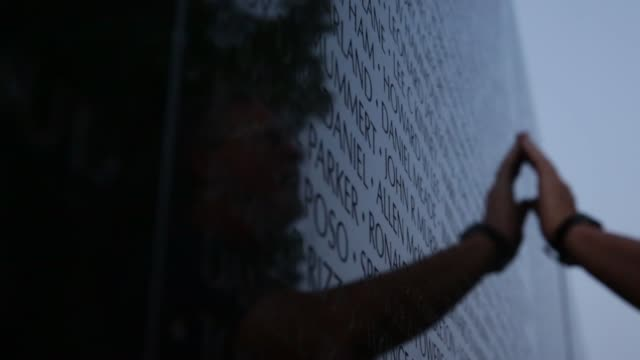 family and friends look up names of their love ones on the wall of the vietnam veterans memorial prior to the memorial day weekend. may 23, 2014.... - vietnam veterans memorial video stock e b–roll