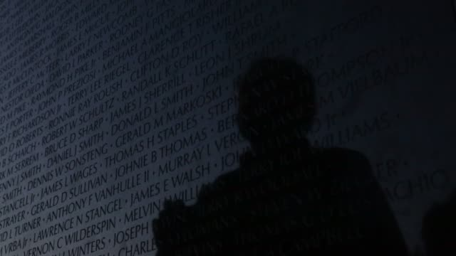 stockvideo's en b-roll-footage met ms family and friends look up names of their love ones on the wall of the vietnam veterans memorial prior to the memorial day weekend may 23 2014... - vietnam veterans memorial