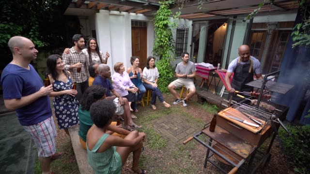 family and friends on enjoying a barbecue party at home - barbecue social gathering stock videos & royalty-free footage