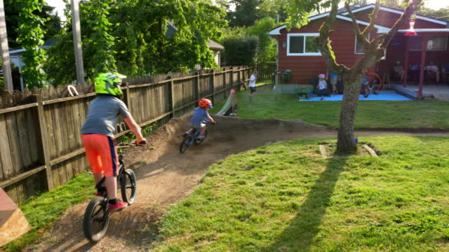 vídeos y material grabado en eventos de stock de ms family and friends playing games and riding bikes in backyard on summer afternoon - familia con cuatro hijos